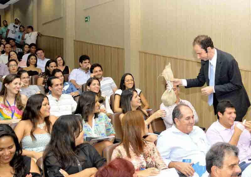 Daniel Bizon entregando um objeto para uma das participantes