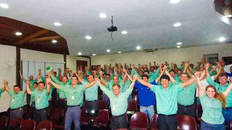 Equipe Vale com os braços para cima na palestra motivacional